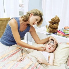 Young Woman Taking Sons Temperature