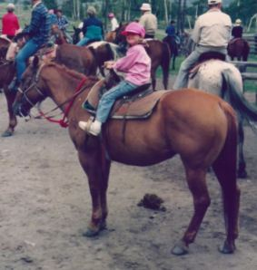 Daughter on Two Cents -- little girl on big horse, and proud of it